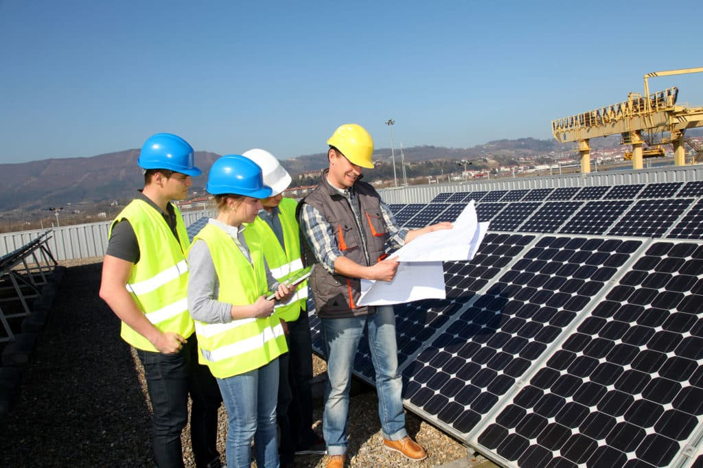 group of electricians with solar panel